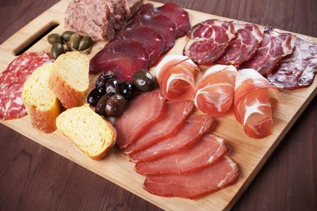 Tablero de charcutería con carne curada, pan y aceitunas Foto de archivo
