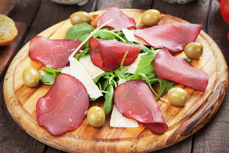 charcutería: Charcuterie board with italian bresaola cured beef meat slices, cheese and rocket salad Foto de archivo