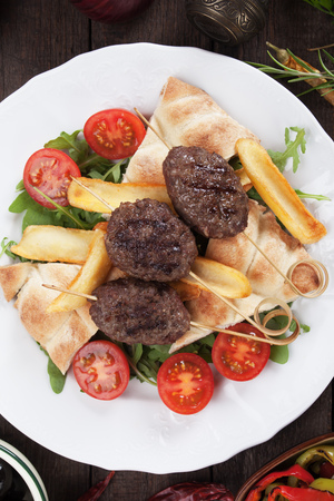 Turkish kofta kebab, minced meat skewer with fried potato and flatbred