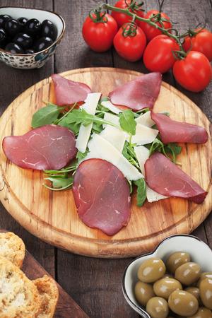charcutería: Placa de charcutería con bresaola italiana, queso grana padano y ensalada de cohetes
