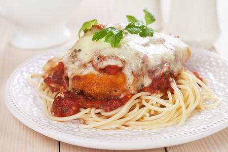 Parmesan chicken with melted cheese and tomato sauce served over spaghetti pasta