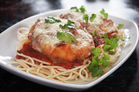 Chicken parmesan with melted cheese and tomato sauce served over spaghetti pasta Standard-Bild