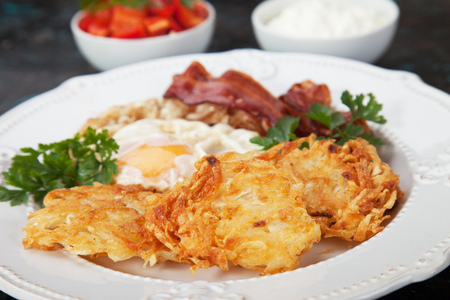 Hash browns, potato pancakes with fried egg and bacon