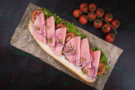 Italian submarine sandwich with cured meat, lettuce and tomato