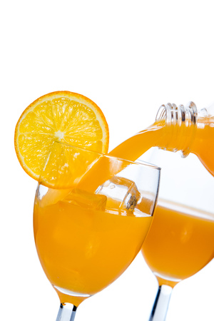 Fresh orange juice poured in glass over white background Stock Photo