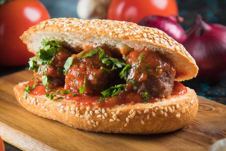 Gehaktballetjes geserveerd in een sesamzaadbroodje met tomatensaus als sandwich
