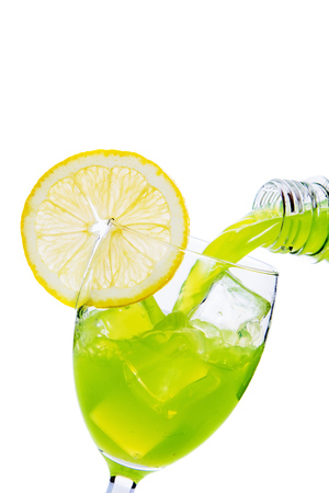 Glass of green apple juice with slice of orange Stock Photo