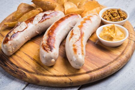Grilled german sausages with mustard and fried potato chips Reklamní fotografie