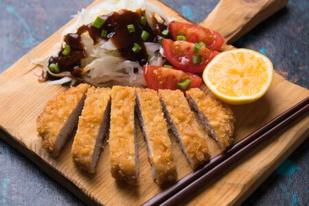 Japanese tonkatsu steak, breaded and fried pork cutlet served with shredded cabbage Stock Photo