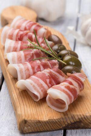 Rouleaux de bacon pancetta servis avec des olives marinées, nourriture antipasti populaire