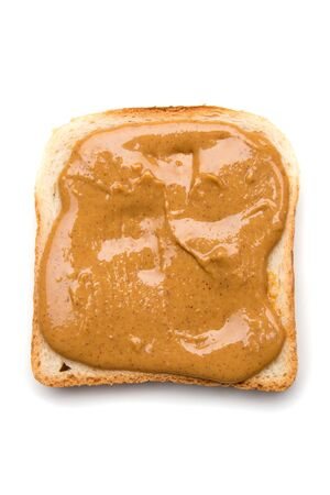 Slice of bread with peanut butter spread on top isolated over white background Imagens