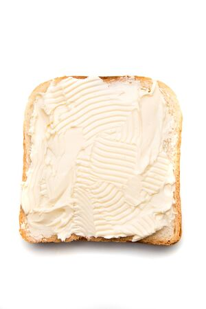 Slice of bread with butter spread on top isolated over white background Imagens