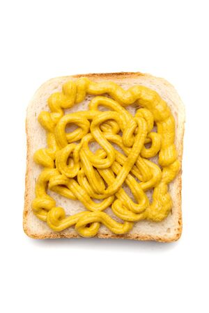 Slice of bread with yellow mustard spread on top isolated over white background Imagens