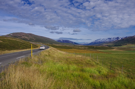 snow covered mountains: Car in the road leading to snow covered mountains, Beautiful landscape in early winter of Iceland Stock Photo