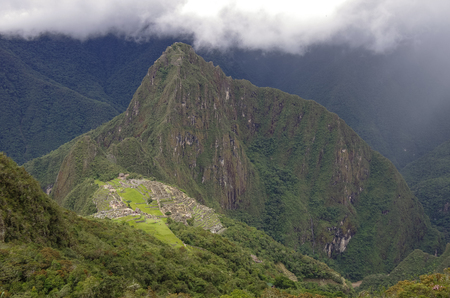 cusco region: View of the Lost Incan City of Machu Picchu and Huayna Picchu mountain from Machu Picchu mountain .Low clouds .Cusco Region,Sacred Valley, Peru
