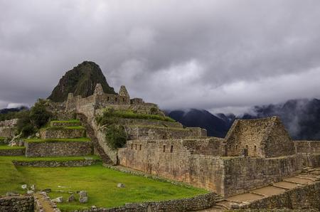 cusco region: View of temple ruins in Lost Inca City of Machu Picchu. Low clouds. Cusco Region,Sacred Valley, Peru
