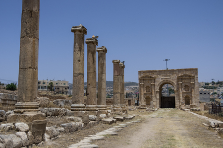 colonnaded: Columns in Colonnaded Street and North Gate at background, Ancient Roman city of Gerasa of Antiquity , modern Jerash, Jordan Stock Photo