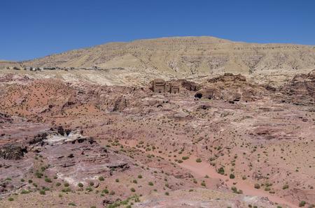 Ruin of Moghar Annassara (Christian Tombs )  in Petra and Uum Sayhoun village at background and dry watercourse of Wadi Mataha river , Jordan Stock Photo