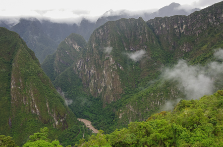 View from  terraces of Lost Inca City of Machu Picchu to canyon of river Urubamba . Low clouds. Cusco Region,Sacred Valley, Peru