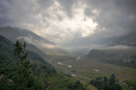 swanetia: View of the Georgian Military Highway and the valley after the storm. The sun shines through the clouds. Georgia, Europe Stock Photo