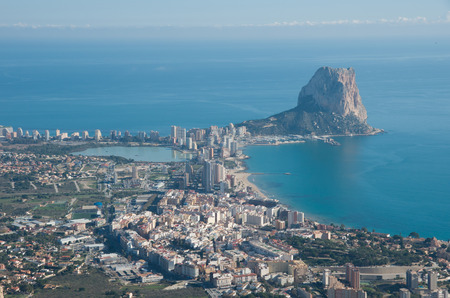 Panorama of Calpe (Calpe) town, Spain. Overlooking the coast, the harbor, lake and Ifach cliff. Shot from top of mountain near town.