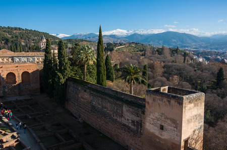 View of courtyard, walls and tower of Alcazaba, citadel of Alhambra, Nasrid with Sierra Nevada mountains in snow at the background . Granada, Spain.