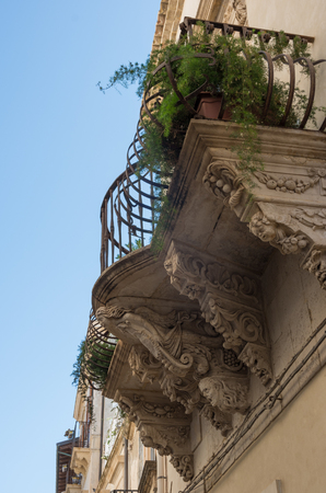 Flowery balconies in old street on the Ortigia island - old town of Syracuse, Sicily, Italy.