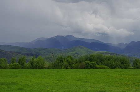 Green meadow with Fagaras mountains range at background, cloudy sky. Carpathians, Romania, Europe