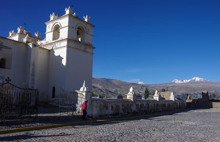 Main square and Church of the Immaculate Conception with mountains behind in Yanque, Colca Canyon, Peru. It was built in 17th century in baroque style. Stock Photo