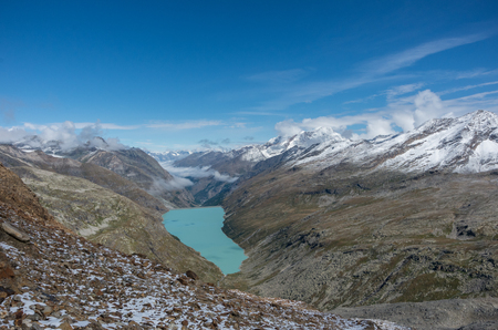 View to Stausee lake near Saas Fee in the southern Swiss Alps from Monte Moro pass, Italy