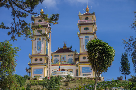 Towers of the Thanh That Da Phuoc on blue sky background. Scenic view of the temple for the Cao Dai religion adherents at Dalat (Da Lat), Vietnam. Dalat is a popular tourist destination of Asia.