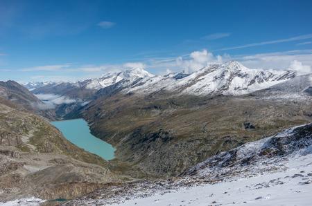 Widok na jezioro Stausee w pobliżu Saas Fee w południowych Alpach Szwajcarskich z przełęczy Monte Moro, Włochy