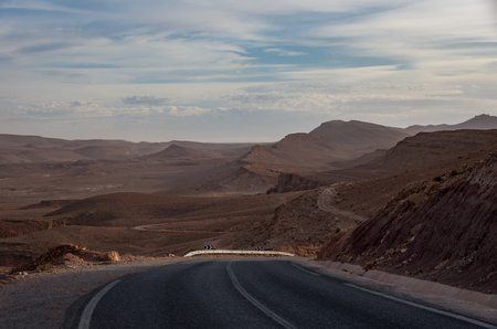 Road from Todgha Gorge near Tinghir city in Morocco. Desert landscape at background. 免版税图像
