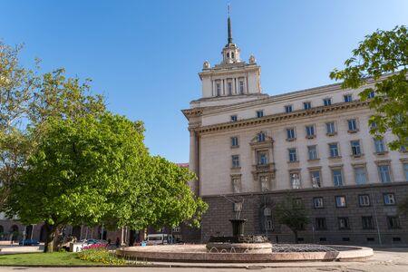 Sofia, Bulgaria - May 3, 2019: Fountain at Atanas Burov Square with National Assembly at background. Sofia, Bulgaria