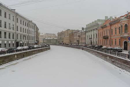 View of the embankment of Moyka river the historical center of Saint-Petersburg, Russia. Winter time with snow and ice.