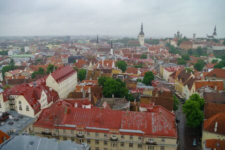 Tallinn Old Town and Toompea Hill, Estonia, panoramic view on rainy weather with traditional red tile roofs, medieval churches and walls.