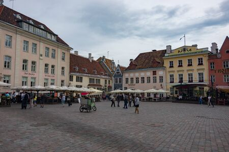 Tallinn, Estonia - July 29, 2017:   Tourists crowd the sidewalk cafes and shops in the medieval Tallinn Town Square in the walled city of Tallinn Estonia.