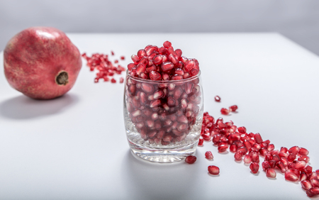 Fresh red pomegranate seeds sprinkled in a glass
