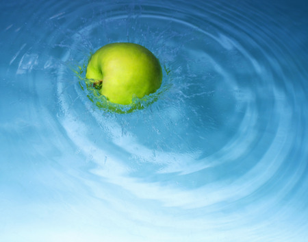 green yellow apple delivers the water surrounded by splashes and drops Stock Photo