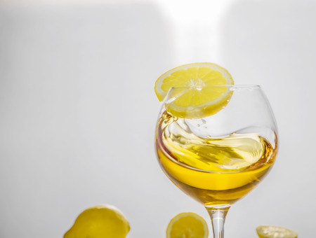 Yellow lemon on a wall of glass with a glass of drink whirlpool Stock Photo