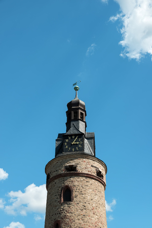 Old stone tower with a clock, against the blue sky