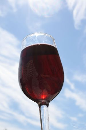 glasswear: red wine in glass on sky background