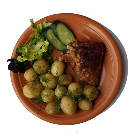 The fried hen in breadcrumbs. On a garnish - a boiled young potato with a butter and fennel. The dish is decorated by salad and fresh cucumbers. photo