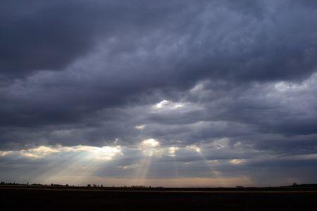 Shafts of light illuminating farmland on a cold dark day
