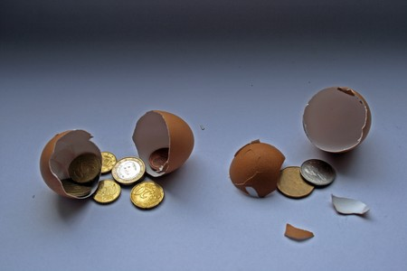 hatched: FinanceInvestment ConceptSeveral euros and canadian coins are being hatched from an egg shell.
