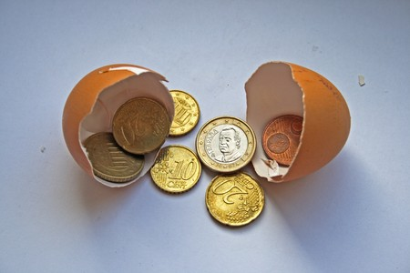 hatched: FinanceInvestment ConceptSeveral euros coins are being hatched from an egg shell. Stock Photo
