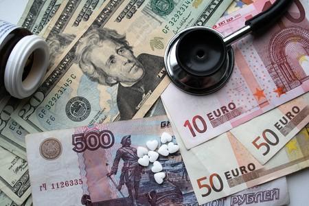 stetoscope: illness of international economic, stetoscope and pills on variouse money background Stock Photo