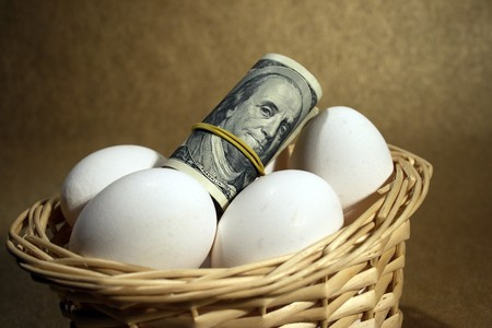 roll of dollars in the basket with eggs photo