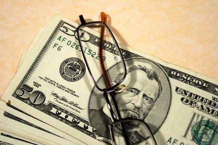 scrutiny: dollars banknotes and glasses