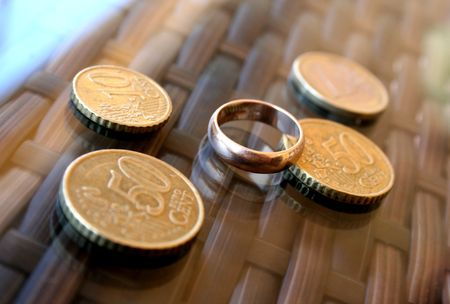 profit celebration: European coins and the wedding ring, laying on a table Stock Photo